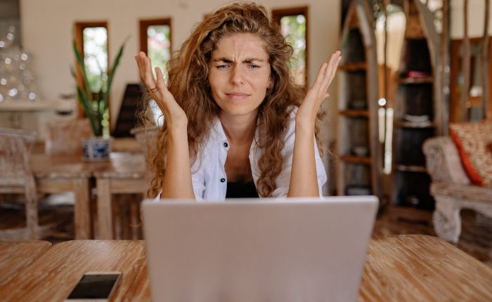 business owner woman sitting in front of laptop frustrated