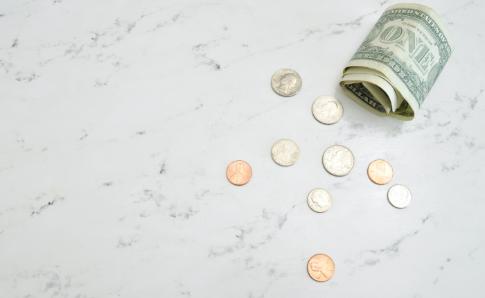 money coins and dollar bill on marble table